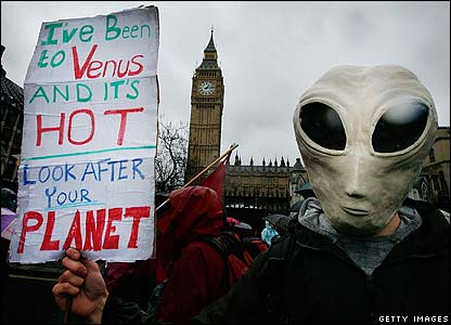 A climate change protester waves a placard outside the Houses of Parliament in London