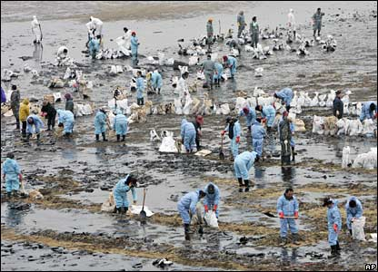 Local residents attempt to clear oil near the Mallipo beach