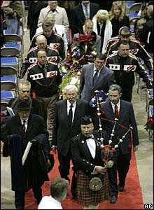 A bagpiper leads pallbearers carrying motorcycle daredevil Evel Knievel