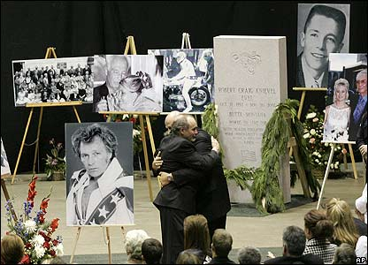 The son of Evel Knievel receives a hug after speaking at his father's memorial service
