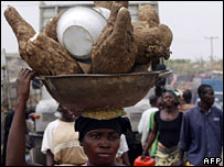 Woman carrying a bowl of yams