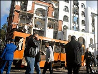 People standing by bomb damaged bus and building