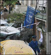 A policeman walks past a damaged UN building in Algiers, 11 December 2007