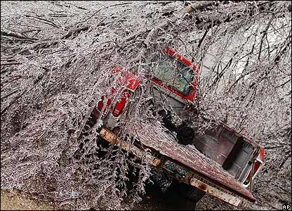 An ice-covered tree covers a pickup truck in Joplin, Missouri