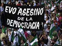 """Opponents of Evo Morales hold up a banner reading """"Evo assassin of democracy"""" during a protest in Santa Cruz on 26 November"""