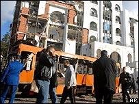 أشخاص إلى جوار الحافلة التي نسفت