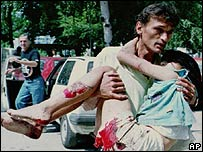 Man carries girl hurt in shelling in Sarajevo (1995)