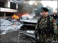 Soldier near bomb damaged vehicles