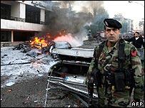 Soldier near bomb damaged vehicles