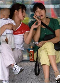 Chinese women share a mobile phone