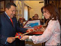 Venezuelan President Hugo Chavez presents Argentine President Cristina Fernandez de Kirchner a replica of the Simon Bolivar sword in Buenos Aires 11 December 2007