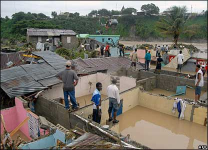 Residents of Santiago, north of Santo Domingo, stand atop the remains of houses, 12 December 2007