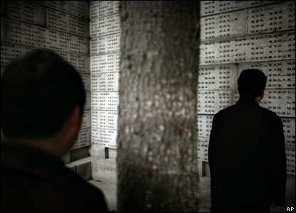 People look at names of victims at the memorial hall