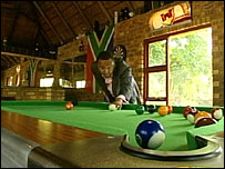 Brian Mdluli in the pool room at his luxury home filmed by BBC TV
