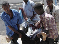 A man wounded in a mortar attack on Bakara market in Somalia is helped to a local hospital (13 December 2007)