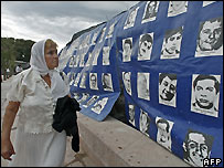 """Argentine woman walks by pictures of people """"disappeared"""" during military rule - file photo"""