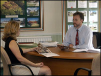 Woman talking to an estate agent in his office