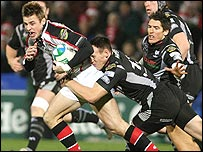 Ulster winger Tommy Bowe is tackled by Mark Taylor of the Ospreys