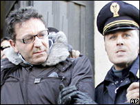 Edoardo Contini (left) is held by an Italian policeman