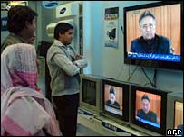 People in Karachi watch as Pakistan's President Pervez Musharraf addresses the nation