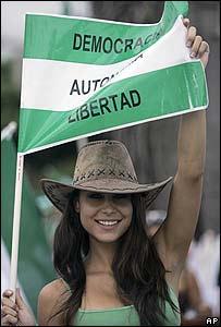 """Una residente de Santa Cruz con una bandera que reza: """"Democracia, Autonomía, Libertad"""""""