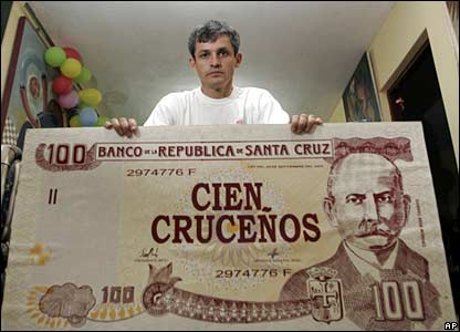 Santa Cruz artist Henry Flores with a painting of a false banknote promoting autonomy