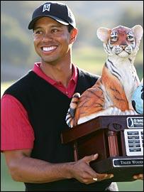 Tiger Woods holds aloft the winner's trophy
