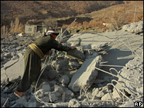 A villager looks through the rubble of Qlatuka village (16 December 2007)