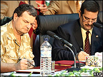 British Major General Graham Binns, the head of British forces in Basra, and Basra governor Mohammed al-Waili sign the Basra handover.