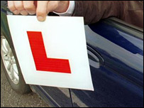 A driver holding an L-plate