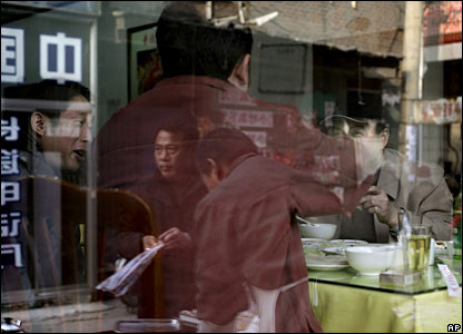 People are reflected on a window of a restaurant in Beijing