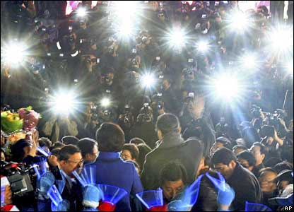 Photographers in Seoul take pictures of President-elect Lee Myung-bak and his wife (centre)