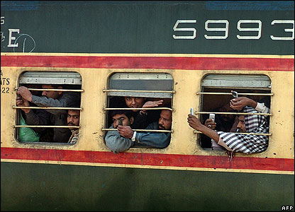 Passing Pakistani train passengers take pictures of the wreckage of a train crash