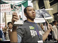 A demonstrator holds a statue of the goddess of democracy during a protest in Macau (20/12/2007)