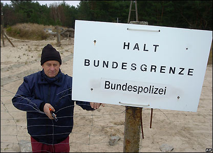 A worker cuts down the fence between Germany and Poland in Ahlbeck, Germany