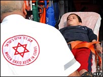 An Israeli medic carries a boy on a stretcher into an ambulance after rockets fired from Gaza landed near a primary school in Sderot on 20 December 2007