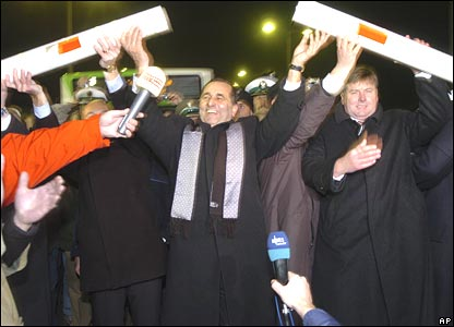 Polish officials raise a dismantled barrier at the German-Polish border in Ahlbeck, northern Germany, on Friday 21 December 2007