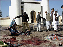 Pakistani security officials search the scene of a bombing 21/12/07