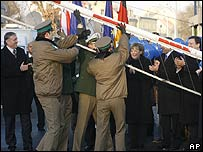 German and Polish border police officers lift a border barrier in Zittau