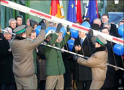 German and Polish border police lift a barrier in Zittau, as the leaders of both countries look on