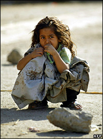 An Iraqi girl crouches in a street in central Baghdad (4 December 2007)
