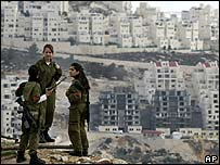 Israeli soldiers stand on a hillside opposite the Har Homa settlement