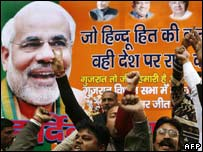 BJP supporters celebrate in front of a Narendra Modi poster