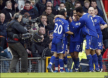 Tim Cahill is mobbed by his Everton team-mates after scoring the equaliser