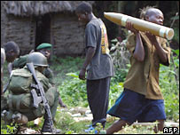 Children help government soldiers carry artillery shells in eastern DRC