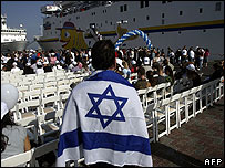 A French Immigrant to Israel wears an Israeli flag over his shoulders after disembarking a cruise ship at the Haifa