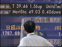 Japanese trader looks at market board in Tokyo - file photo 12 December 2007