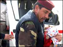 An Iraqi soldier rushes a wounded child into a hospital in the restive city of Baquba