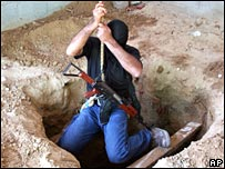 A masked Palestinian descends into a tunnel dug near the separation barrier between Egypt and the southern Gaza Strip on Monday 24 December 2007