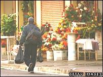 Homeless man walks past flower shop in Skid Row, LA